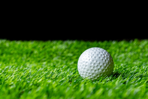 Piłka golfowa na trawie w czerni