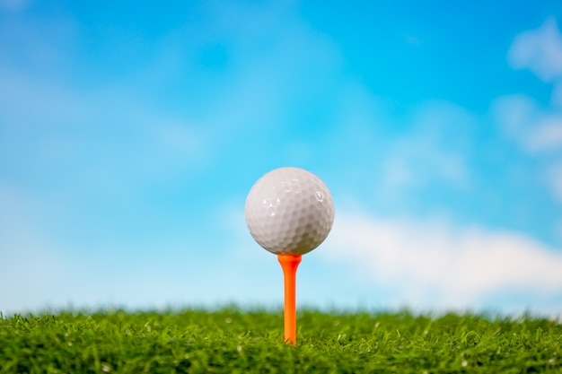 Piłka golfowa na trójniku w polu golfowym na niebieskim niebie