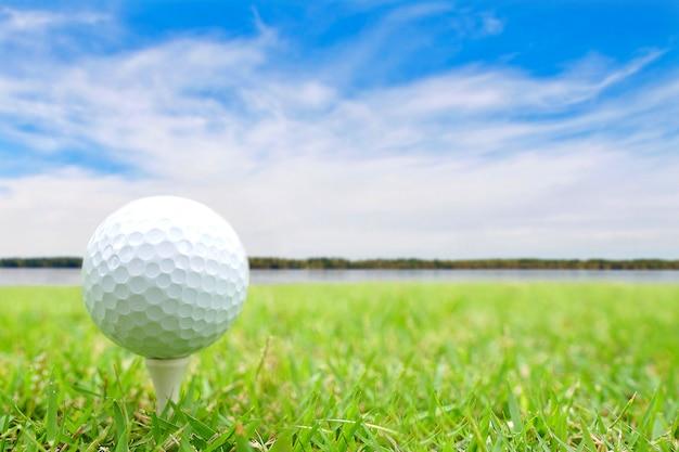Piłka golfowa na trójniku w zielonej trawie.