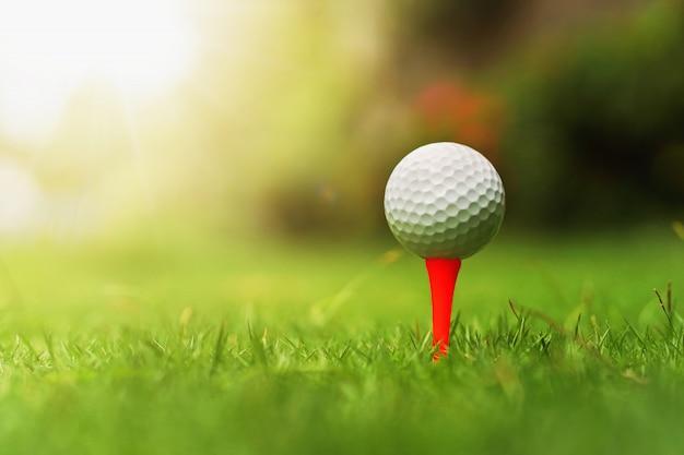 Piłka golfowa na zielonej trawie z wschodem słońca
