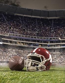Piłka graczy futbolu amerykańskiego z kaskiem na tle stadionu