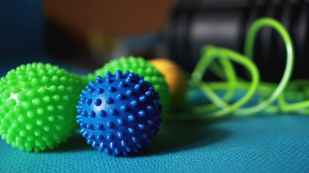 Piłka i wałek masujący do samodzielnego masażu, refleksologii i rozluźnienia mięśniowo-powięziowego, niebieskie tło. sprzęt do uprawiania sportu, jogi, fitness