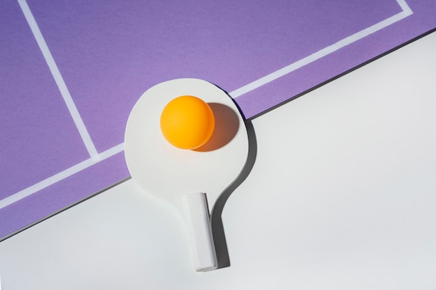 Piłka leżąca płasko na wiosle do ping ponga
