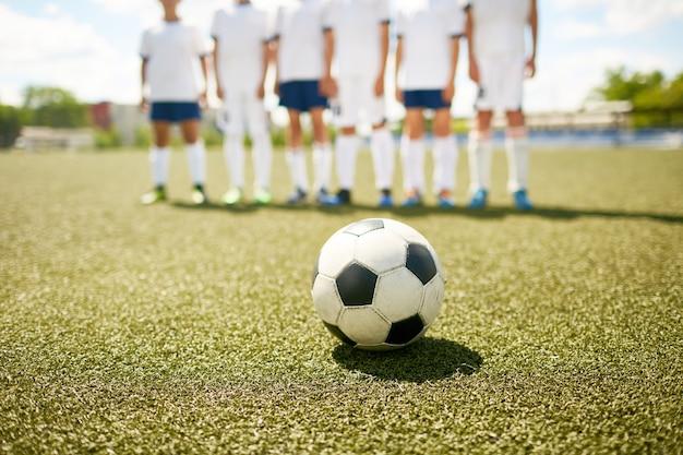 Piłka na trawie w boisku piłkarskim