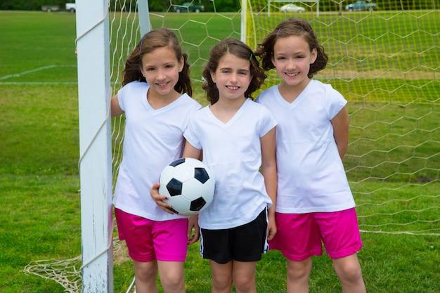 Piłka nożna dzieciaka futbolowe dziewczyny zespalają się przy sporta fileld
