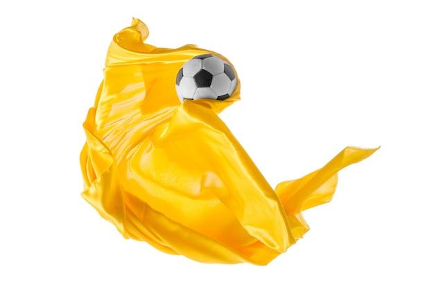Piłka nożna i gładka elegancka przezroczysta żółta tkanina na białym tle lub oddzielona na białym studio