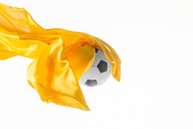 Piłka nożna i gładka elegancka przezroczysta żółta tkanina na białym tle lub oddzielona na białym