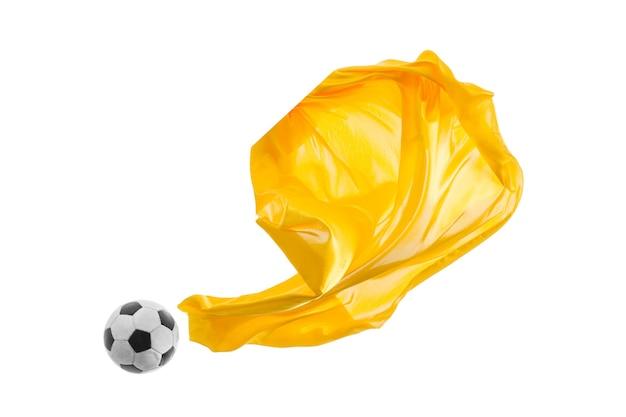 Piłka nożna i gładkie eleganckie przezroczyste żółte tkaniny na białym tle lub oddzielone na tle białego studia.