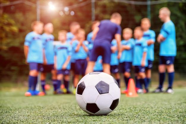 Piłka nożna i niewyraźna drużyna piłki nożnej młodzieży z trenerem na boisku