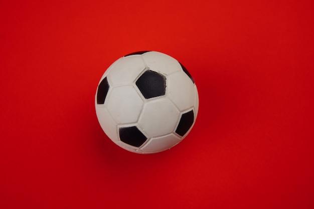 Piłka nożna na czerwonym tle.
