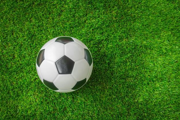 Piłka nożna na zielonej trawie.
