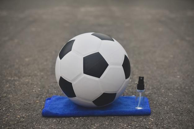 Piłka nożna piłka nożna i alkoholowy spray do czyszczenia wirusa koronowego covid 19, nowa normalna
