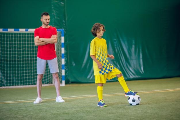 Piłka nożna. słodki chłopak w żółtym mundurze gra w piłkę nożną, jego trener obserwuje go