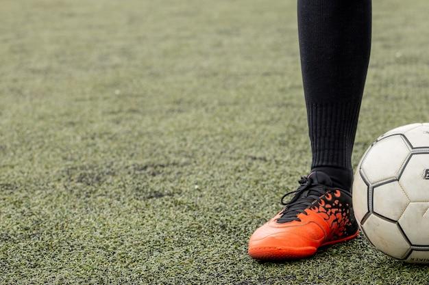 Piłka nożna z nogami na boisku piłkarskim.
