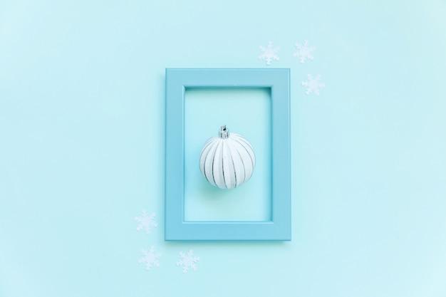 Piłka ozdoba obiektów zimowych w niebieskiej ramce na białym tle na niebieskim tle