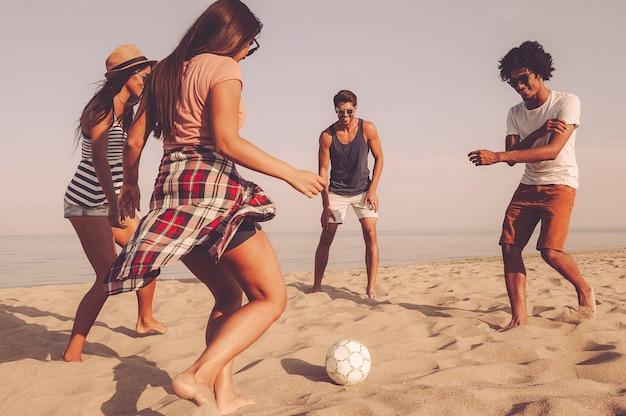 Piłka plażowa. grupa wesołych młodych ludzi bawiących się piłką nożną na plaży z morzem w tle