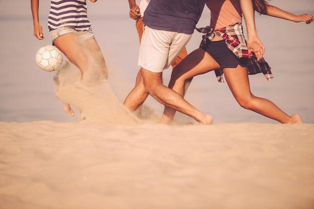 Piłka plażowa w ruchu. przycięty obraz młodych ludzi bawiących się piłką nożną na plaży