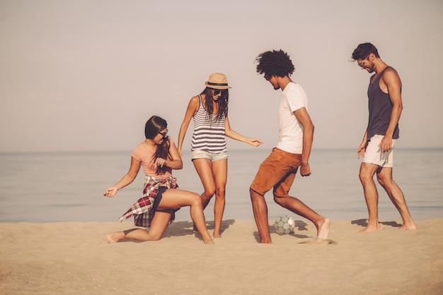 Piłka plażowa z przyjaciółmi. grupa wesołych młodych ludzi bawiących się piłką nożną na plaży z morzem w tle