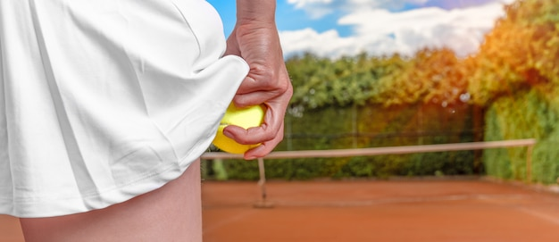 Piłka tenisowa w ręce kobiety w spódnicy na korcie tenisowym. przygotowanie do podania balonu w tenisa. baner z miejsca na kopię