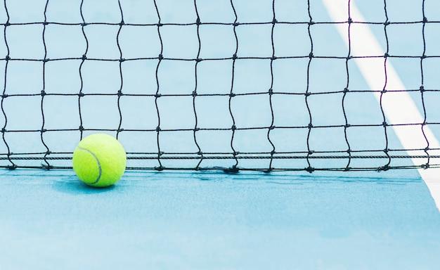Piłka tenisowa z czarnym tle ekranu netto na twardym niebieskim korcie tenisowym