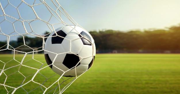 Piłka w bramce. piłka nożna o zachodzie słońca. koncepcja sukcesu.