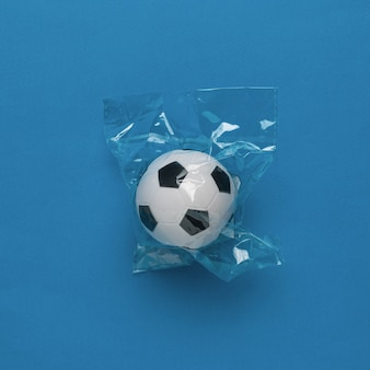 Piłka w celofanowym opakowaniu na niebieskim tle. pojęcie popularnej gry.