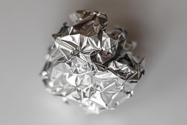 Piłka z gniecionej folii srebrnego koloru z bliska na szarym tle
