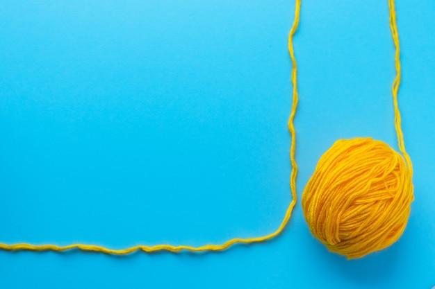 Piłka z żółtej przędzy wełnianej na jasnym niebieskim tle. koncepcja dziewiarskich, ręcznie robionych i hobby. widok płaski świeckich, z góry z miejsca na kopię.