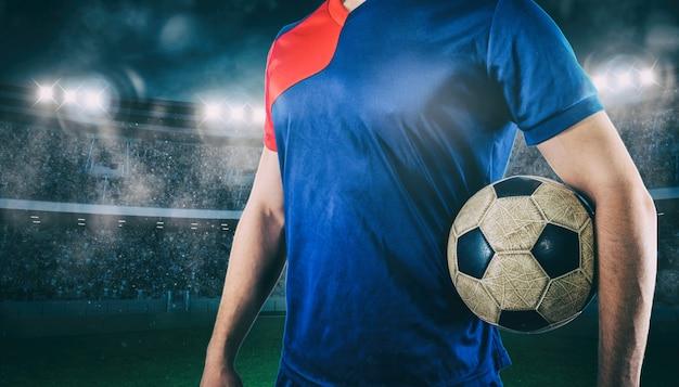 Piłkarz gotowy do gry z piłką w rękach na stadionie