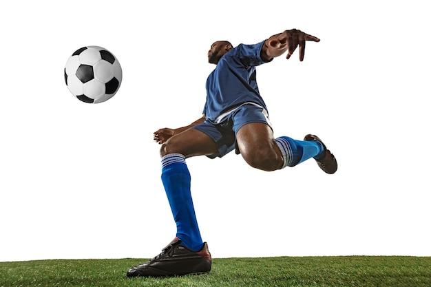 Piłkarz lub piłkarz na białym tle z trawą. młody mężczyzna sportowy model szkolenia, ćwiczenia. atakowanie, łapanie. pojęcie sportu, rywalizacji, zwycięstwa, ruchu, pokonywania. szeroki kąt.