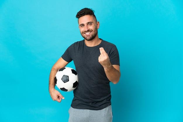 Piłkarz na białym tle na niebieskim tle robi gest pieniędzy
