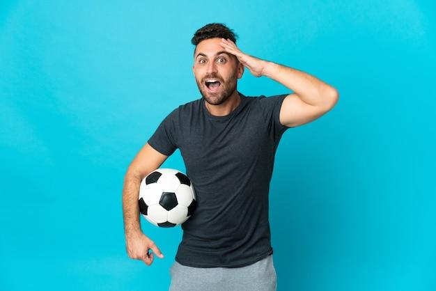 Piłkarz na białym tle na niebieskim tle z wyrazem zaskoczenia