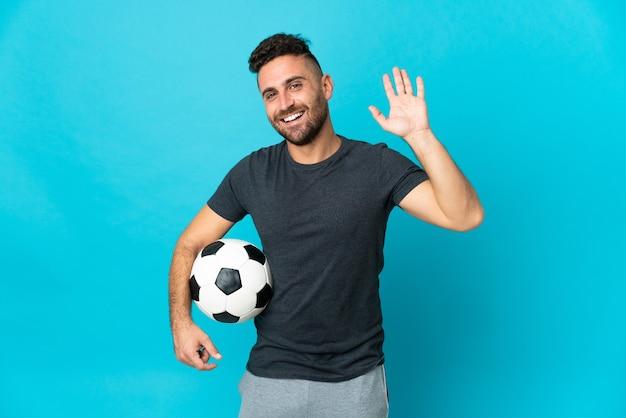 Piłkarz odizolowany na niebieskim tle salutujący ręką ze szczęśliwym wyrazem twarzy