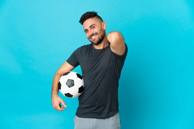 Piłkarz odizolowany na niebieskim tle śmiejąc się