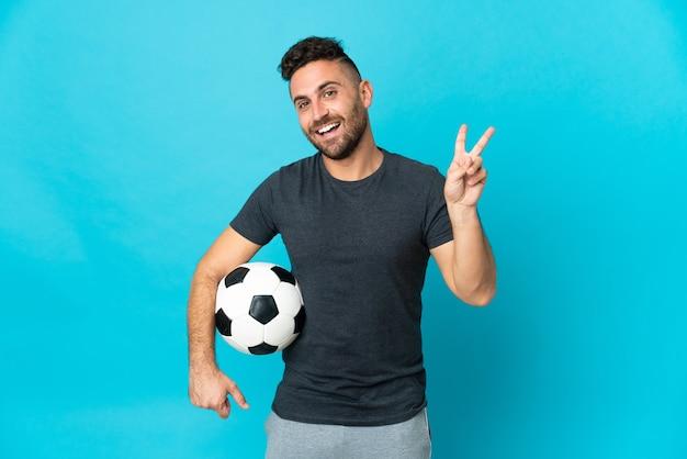 Piłkarz odizolowany na niebieskim tle uśmiechający się i pokazujący znak zwycięstwa