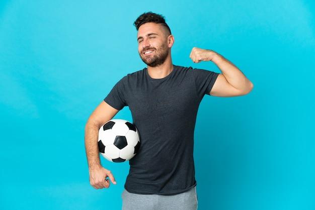 Piłkarz odizolowany na niebieskim tle wykonujący silny gest