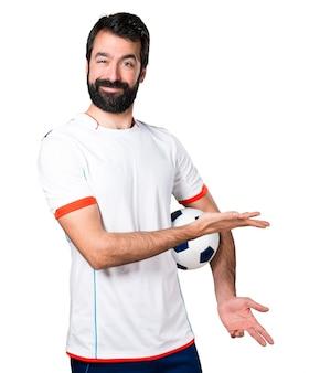 Piłkarz posiadania piłka nożna prezentujących coś