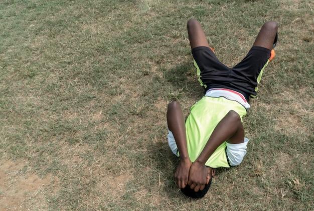 Piłkarz siedzi na polu