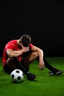Piłkarz siedzieć z piłką na trawie, przegrany mecz