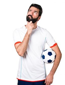 Piłkarz trzyma piłkę nożną myślenia