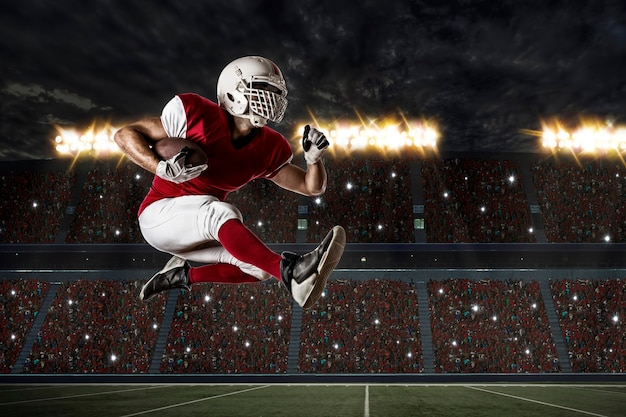 Piłkarz w czerwonym mundurze działa na stadionie.