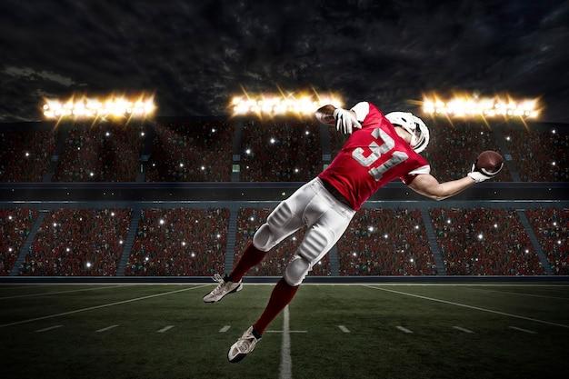 Piłkarz w czerwonym mundurze, łapiąc piłkę na stadionie.