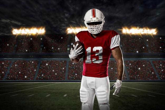 Piłkarz w czerwonym mundurze na stadionie.
