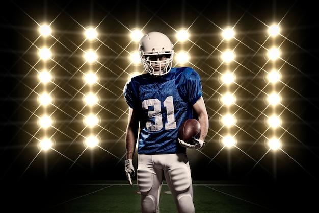 Piłkarz w niebieskim mundurze przed światłami
