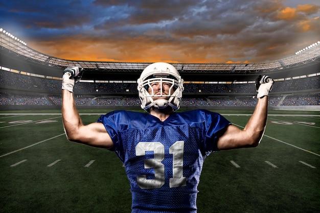 Piłkarz w niebieskim mundurze świętujący z kibicami.