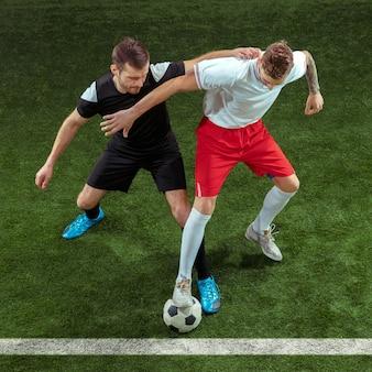 Piłkarz walczący o piłkę na zielonej trawie