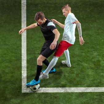 Piłkarz walki o piłkę na tle zielonej trawie.