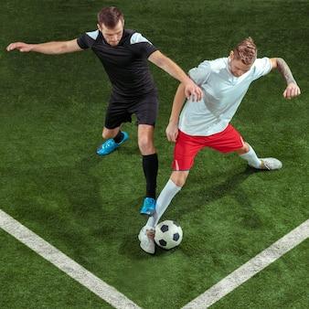 Piłkarz walki o piłkę na tle zielonej trawy. profesjonalni piłkarze płci męskiej w ruchu na stadionie. dopasuj skaczących mężczyzn w akcji, skacz, ruch w grze.