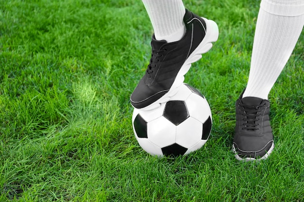 Piłkarz z piłką nożną na zielonej trawie na zewnątrz