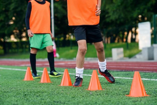 Piłkarze biegający wśród plastikowych pomarańczowych pachołków na sztucznym stadionie